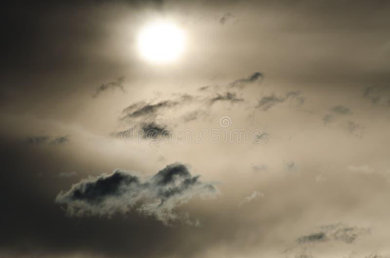 Солитарные слойки облака плавая за заходящим солнцем стоковое фото rf