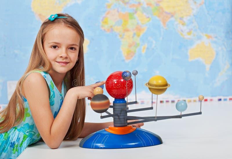 Солнечная система исследования маленькой девочки в классе науки стоковое фото