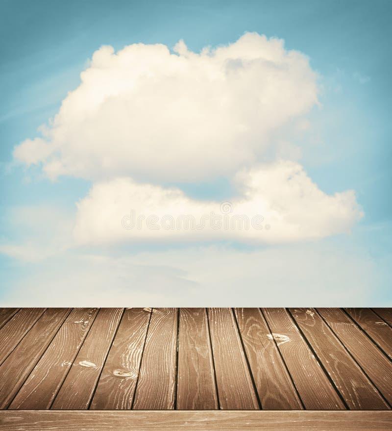 Солнечное небо с облаками и деревянной предпосылкой пола стоковое изображение