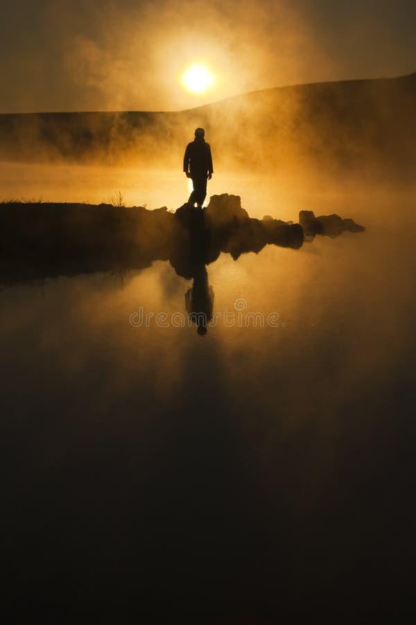 Солнечность утра и Hiker тумана Silhouetted Surround на спокойном озере стоковые фотографии rf
