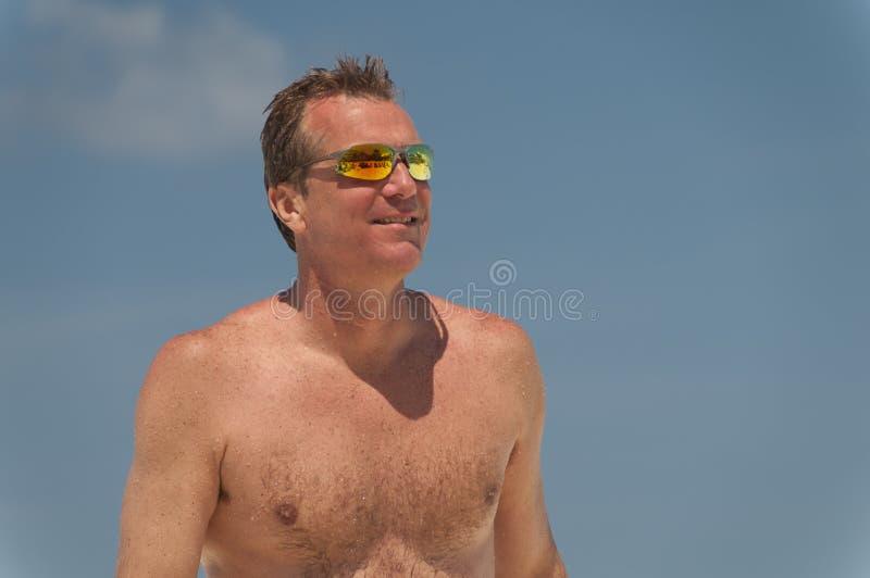 Солнечные очки без рубашки человека нося на пляже. стоковое фото