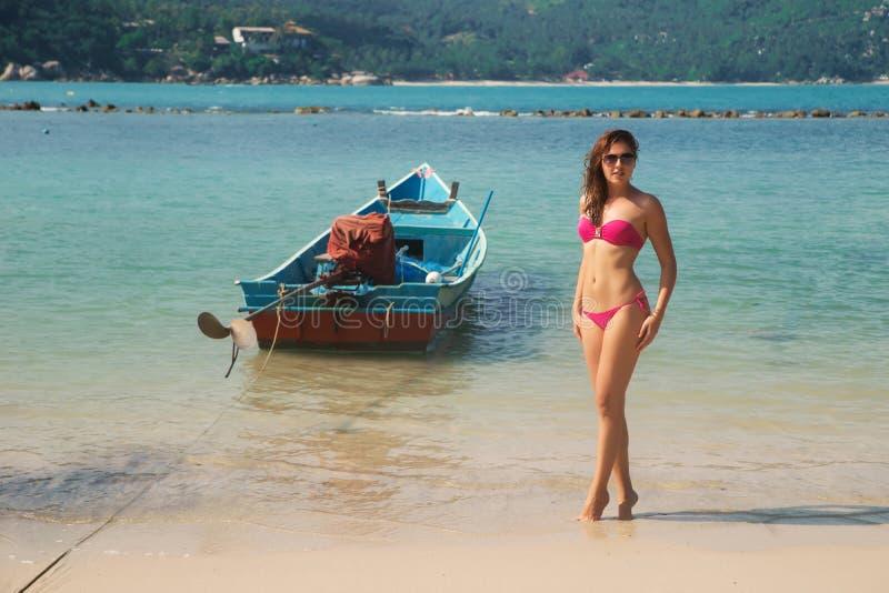 Солнечные очки горячей, сексуальной женщины нося и розовое бикини представляя на береге моря стоковая фотография
