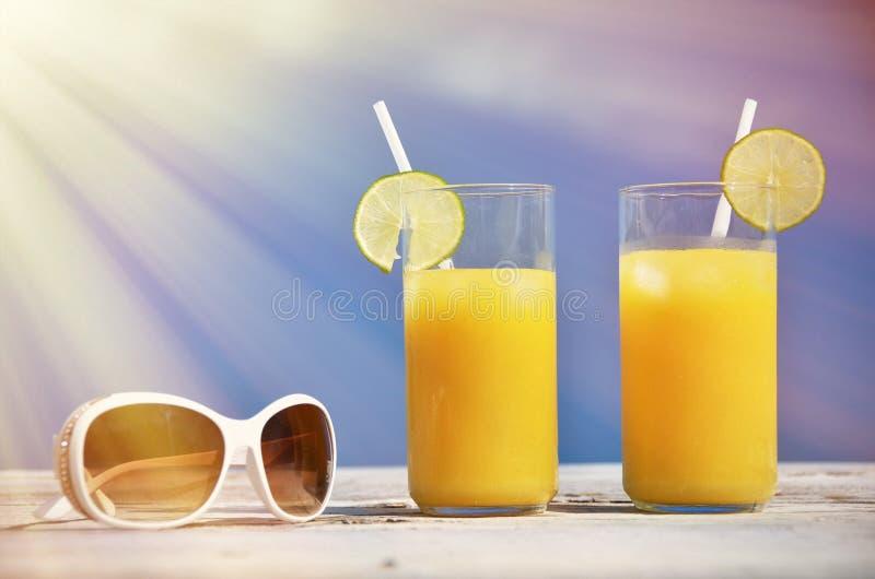 Солнечные очки и апельсиновый сок стоковые изображения rf
