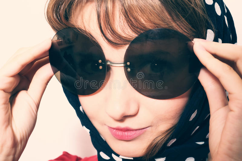 Солнечные очки и головной платок молодой женщины нося стоковая фотография rf