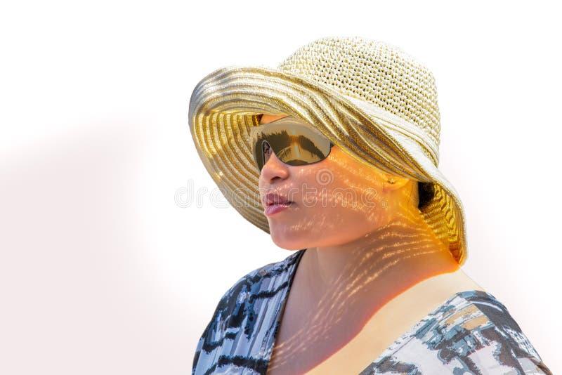 Солнечные очки молодой женщины нося и шляпа солнца смотря солнце поднимают стоковые фотографии rf