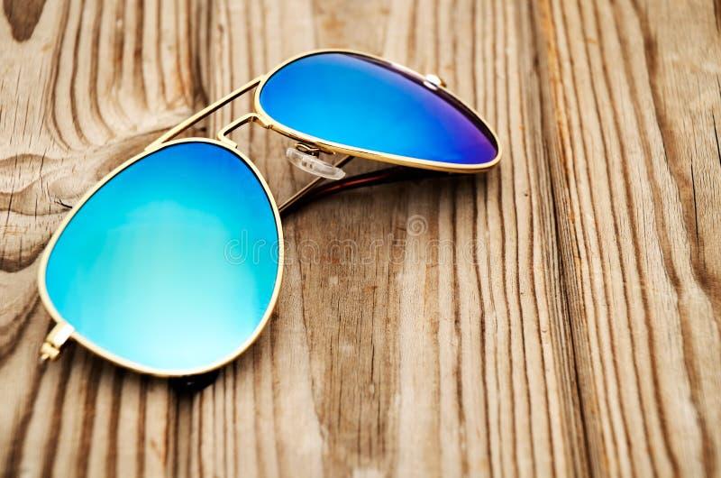 Солнечные очки отраженные синью на деревянном конце предпосылки вверх стоковые изображения rf