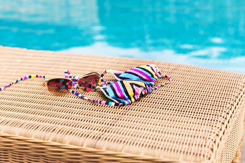 Солнечные очки с купальником на lounger солнца около бассейна стоковое изображение