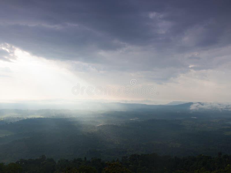 Солнечный свет светит через облака в горы и лес стоковые фотографии rf