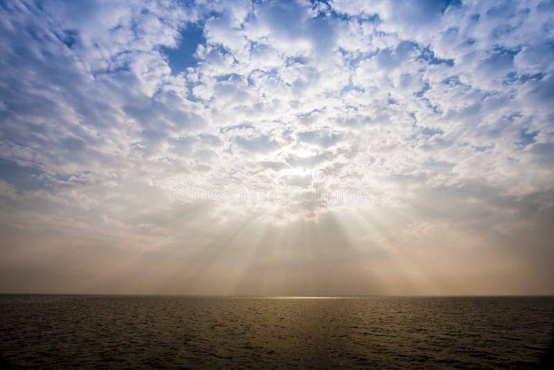 Солнечный луч через помох на небе над морем стоковая фотография rf