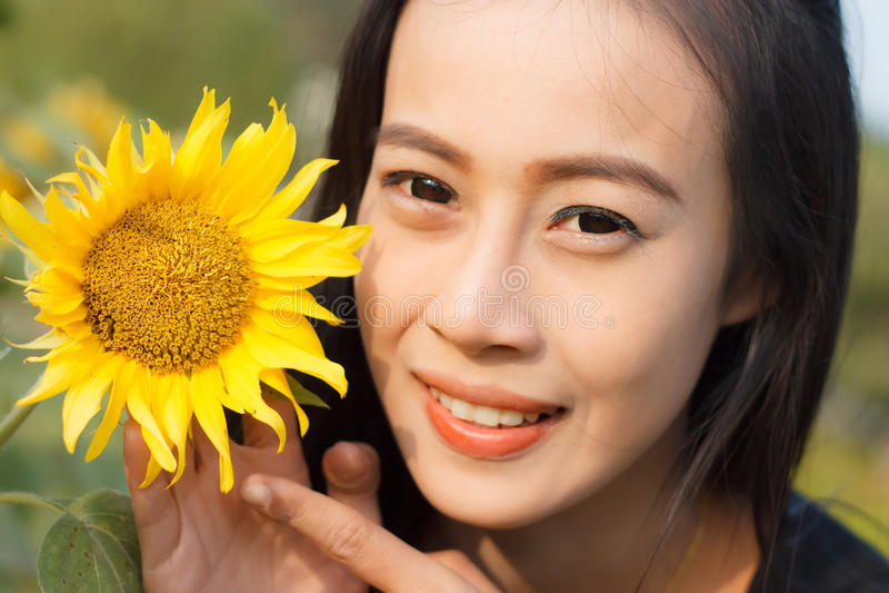 Солнцецвет красивой женщины усмехаясь стоковые фото