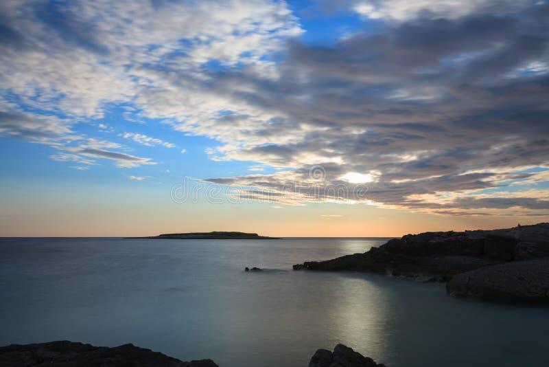 Солнце за облаками над уровнем моря во времени захода солнца стоковое изображение rf