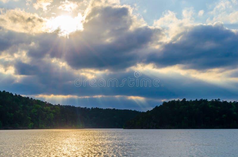 Солнце излучает течь через драматические облака с видом на озеро стоковая фотография rf