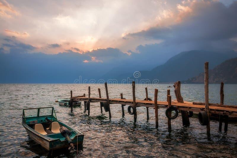 Солнце испускает лучи на заходе солнца на озере Atitlan, Гватемале - взгляде от доков стоковые изображения rf