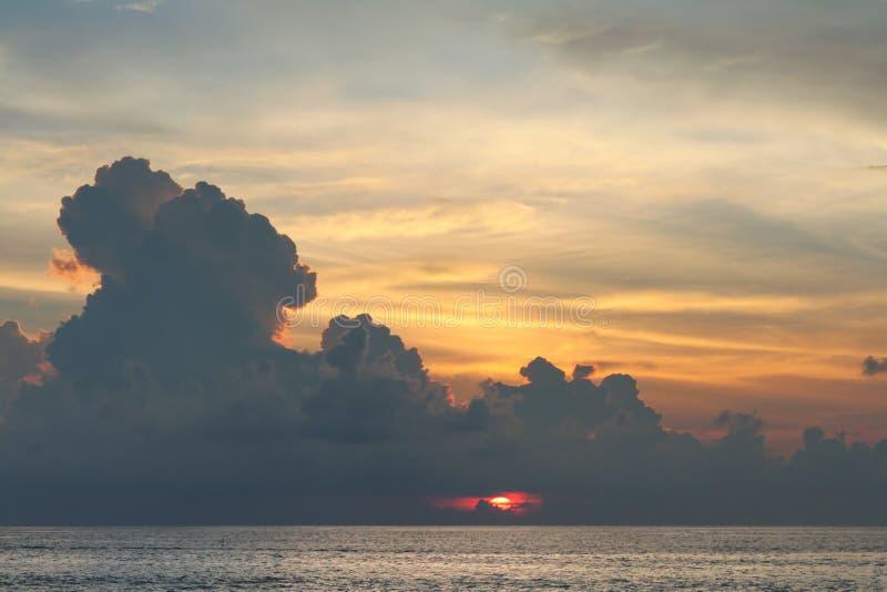 Солнце исчезает за величественными облаками на заходе солнца стоковые фото