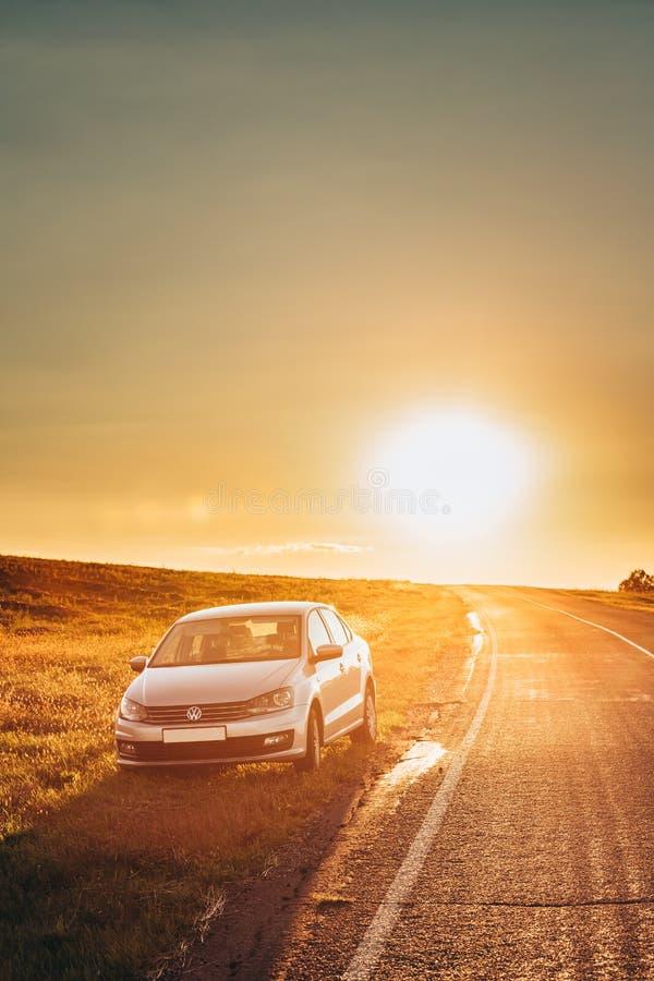 Солнце поднимая над автомобилем седана VW Volkswagen Polo Vento паркуя близко стоковое фото rf