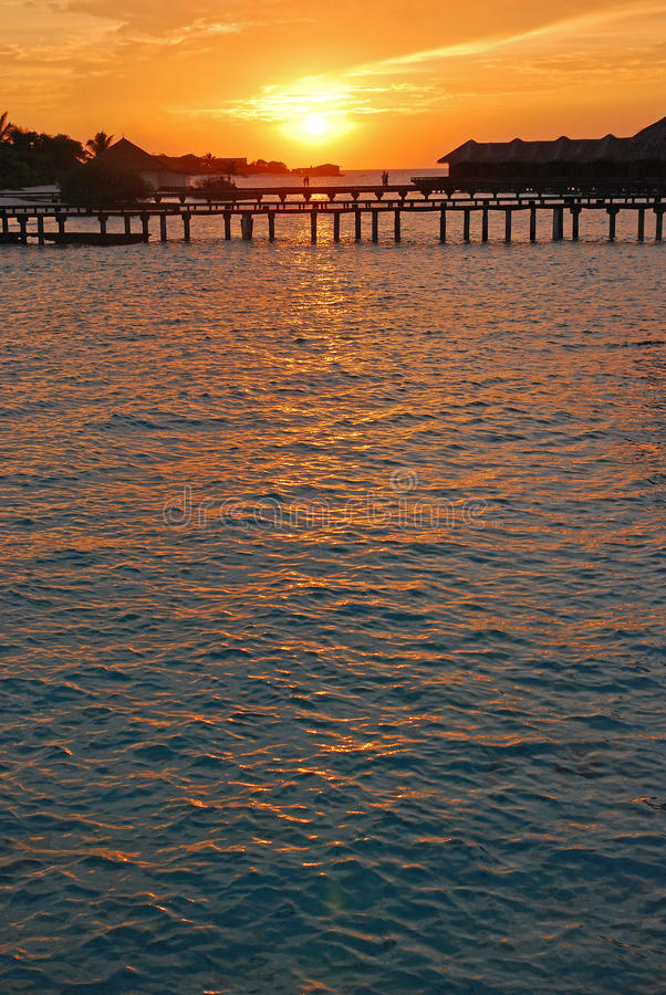 Солнце устанавливая над виллой overwater стоковое фото