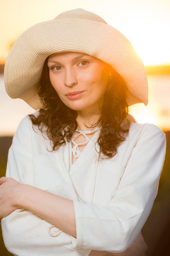 Соломенная шляпа женщины нося усмехаясь и имея потеху против захода солнца стоковое фото