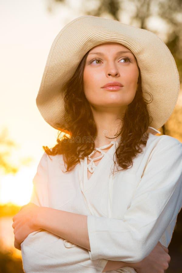 Соломенная шляпа женщины нося усмехаясь и имея потеху стоковые фотографии rf