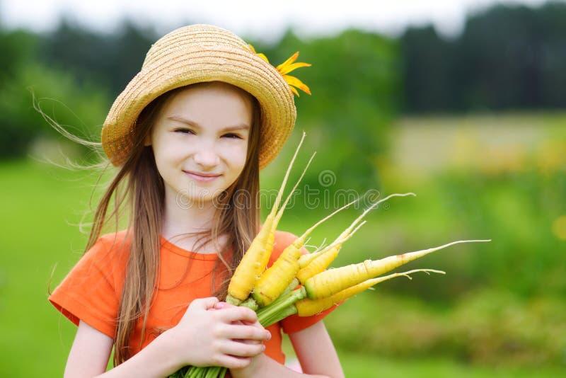 Соломенная шляпа милой маленькой девочки нося держа пук свежих органических морковей стоковое изображение
