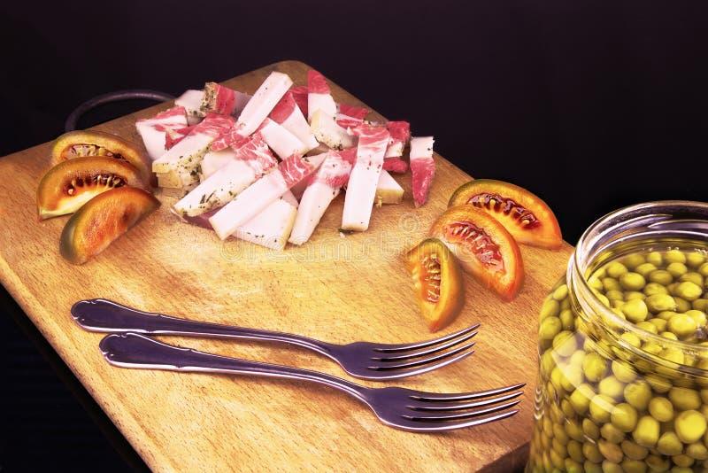Солёное сало свинины с томатами и 2 вилками на доске стоковое фото
