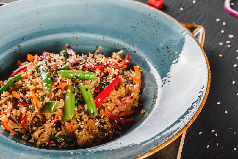 Спагетти макаронных изделий с соусом, овощами тушеного мяса и семенами в плите на темной каменной таблице Вегетарианские лапши, и стоковое фото rf
