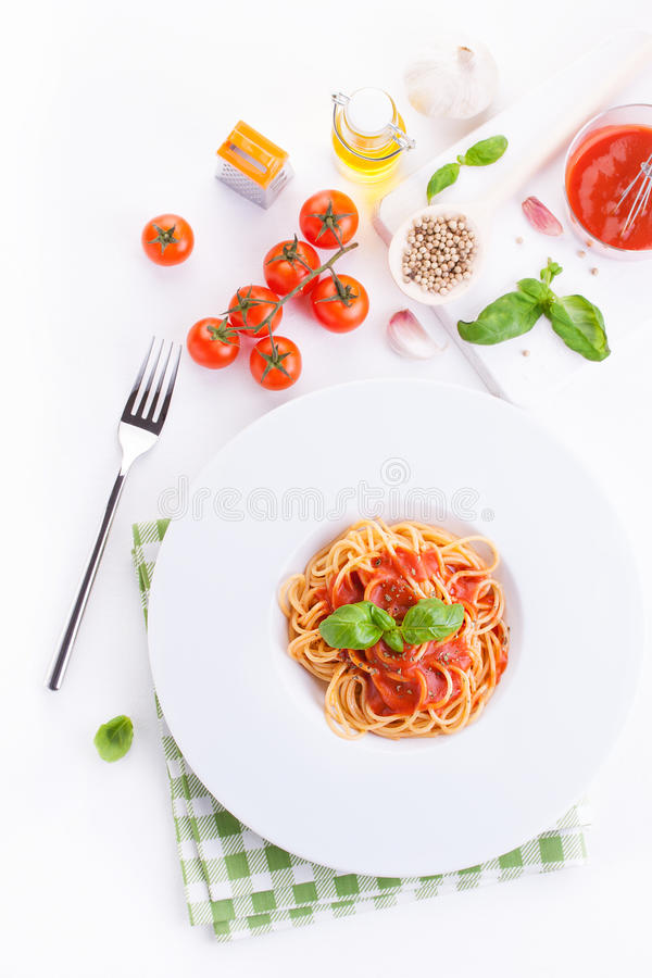 Спагетти макаронных изделий томата с свежими томатами, базиликом, итальянскими травами и оливковым маслом в белом шаре на белой д стоковое фото