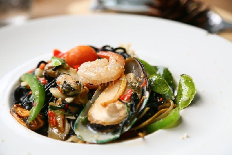 Спагетти с креветками и морепродуктами на белой плите, черном спагетти с морепродуктами на таблице в ресторане, пряных спагетти в стоковые изображения