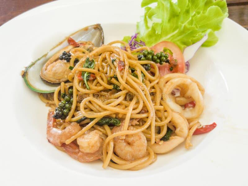 Спагетти с пряными смешанными морепродуктами на белой плите стоковые фотографии rf