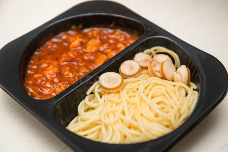 Спагетти с томатным соусом в черной пластичной коробке стоковое изображение rf