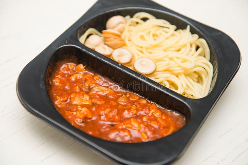 Спагетти с томатным соусом в черной пластичной коробке стоковая фотография