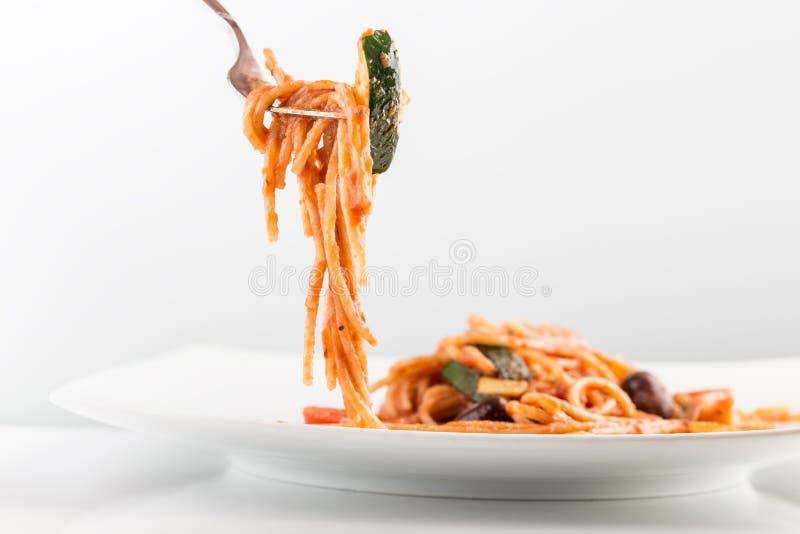 Спагетти с томатным соусом и courgette на вилке стоковые изображения