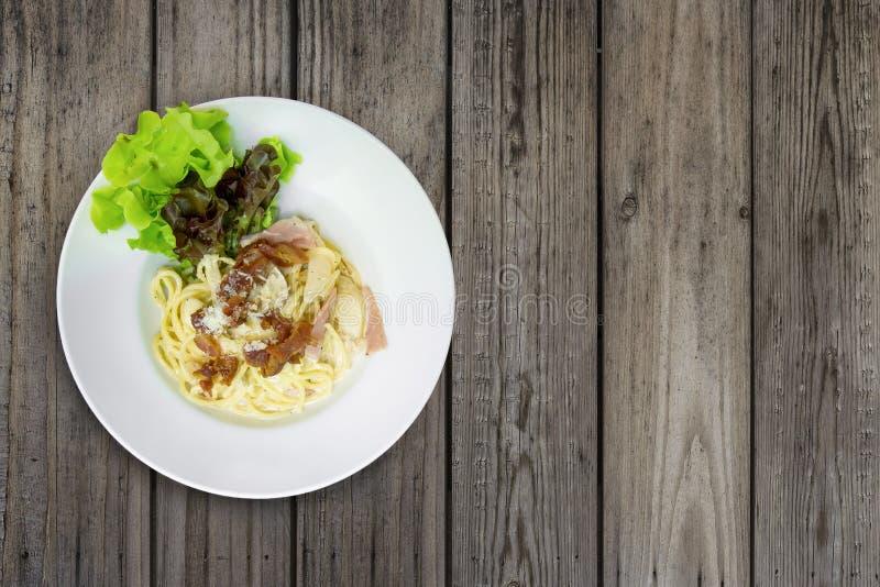 Спагетти Carbonara с беконом и сыром в белой плите на древесине стоковые изображения