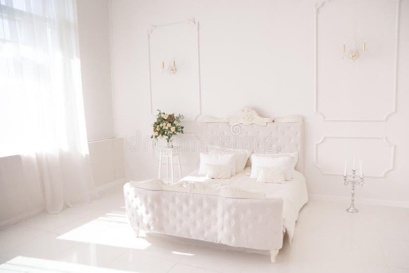 Спальня в мягких светлых цветах Большая удобная двуспальная кровать в элегантной классической спальне стоковое изображение