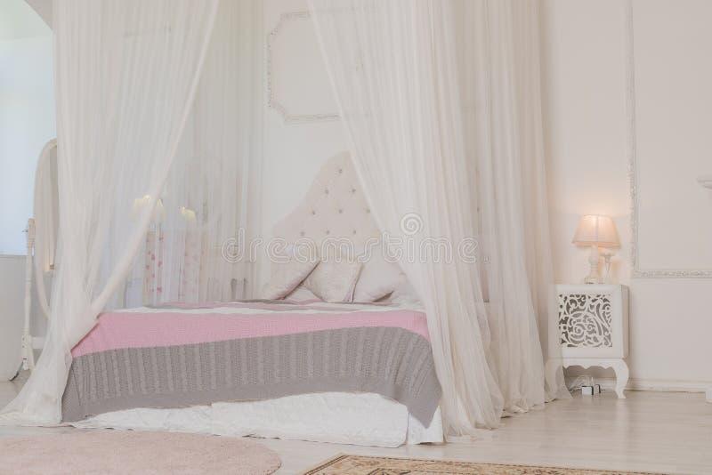 Спальня в мягких светлых цветах с деревянным полом Большая удобная двуспальная кровать 4 плакатов в элегантной классической спаль стоковая фотография