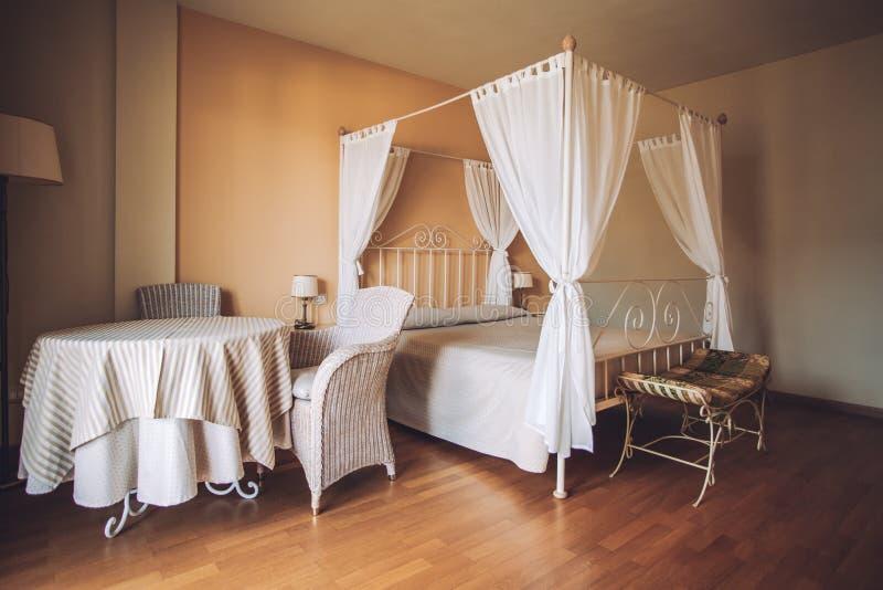 Спальня в светлых цветах Большая удобная двуспальная кровать в элегантном классическом интерьере стоковое фото