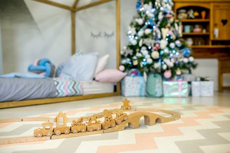 Спальня детей украшенная для рождества Деревянная железная дорога игрушки на предпосылке светов и кровати рождественской елки Рож стоковая фотография rf