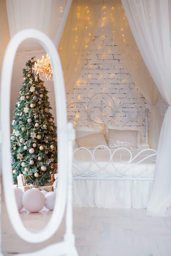 Спальня рождества в мягких светлых цветах Большая удобная двуспальная кровать в элегантном классическом интерьере стоковое фото rf