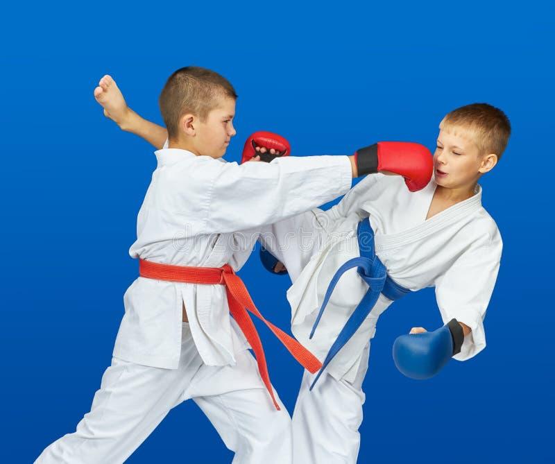Спаренная тренировка в поездах спортсменов karategi с верхними слоями на его руках стоковое фото