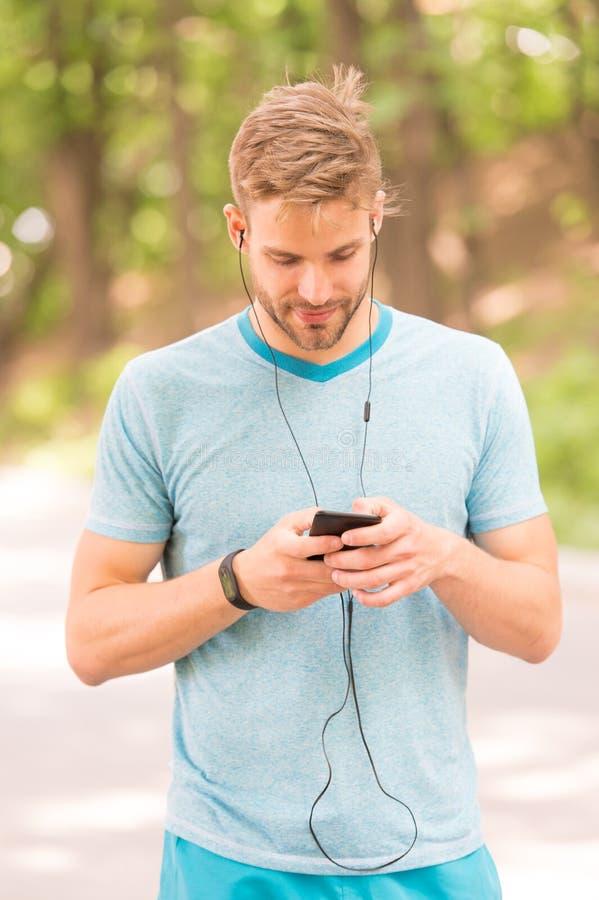 Спаривать его дозор фитнеса с его смартфоном Спортсмен используя отслежыватель фитнеса для тренировки на открытом воздухе Отслежи стоковая фотография rf