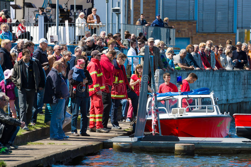 Спасательная служба моторной лодки и зрители на портовом районе стоковые изображения