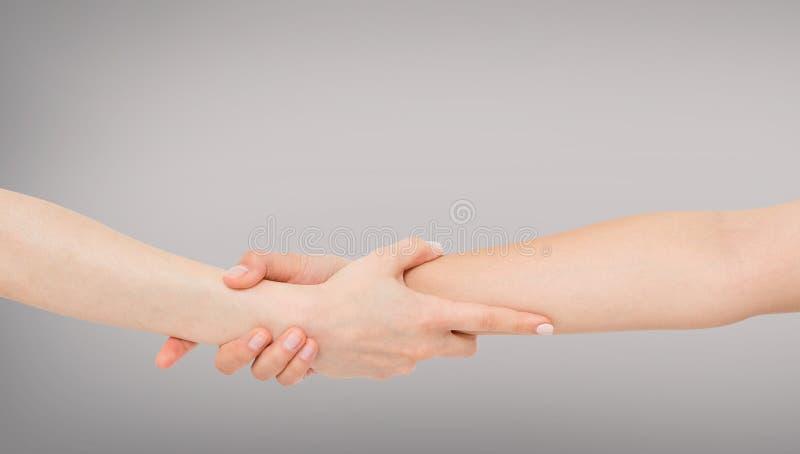 Спасать и помогать путем удержание или сжимать предплечья Рука и рука вытягивая вверх Концепция помощи, любов, приятельства стоковое фото rf