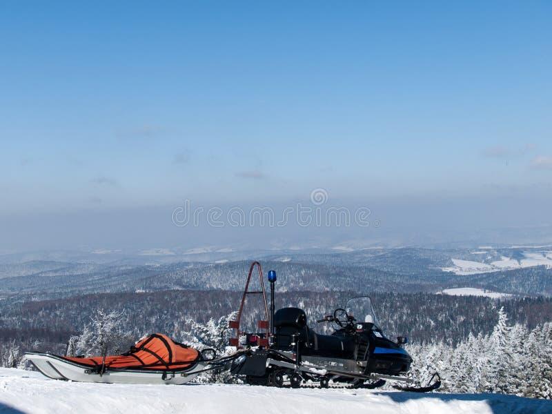 Спасение снегохода в горах стоковое фото