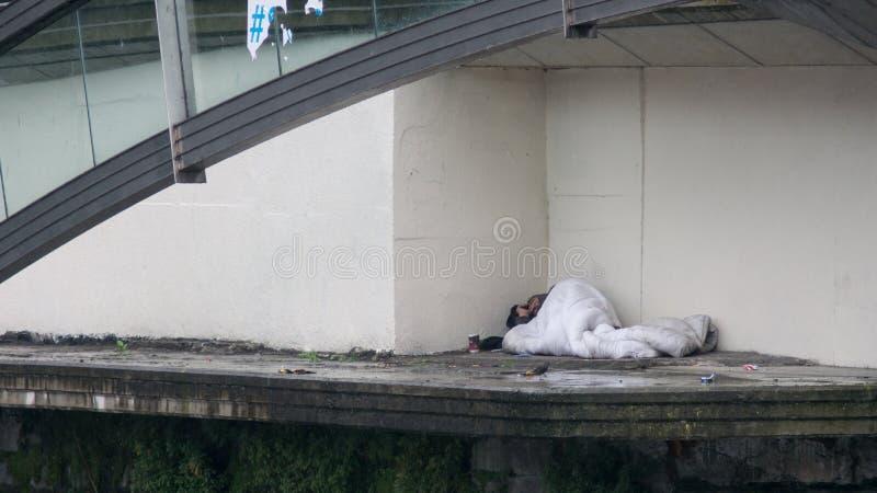 Спать бездомного человека грубый под мостом в Дублине, Ирландии стоковое изображение
