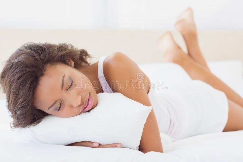 Спать брюнет лежа на кровати держа подушку стоковые изображения rf