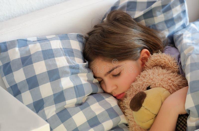 Спать девушка обнимая плюшевый медвежонка стоковая фотография rf
