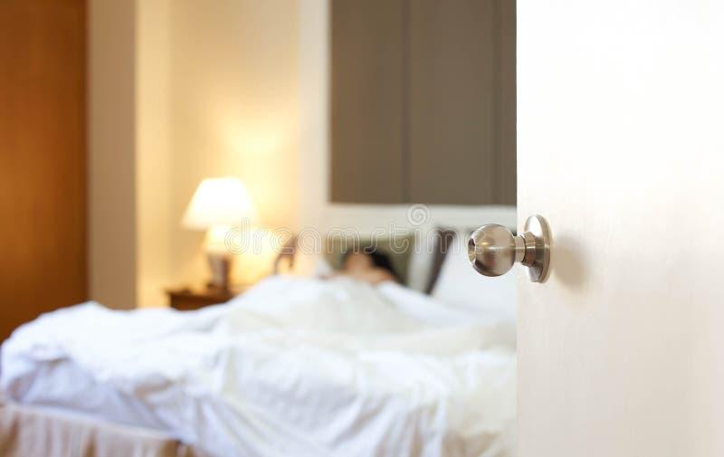 Спать женщина отдыхая в кровати с дверью раскрывает стоковое фото