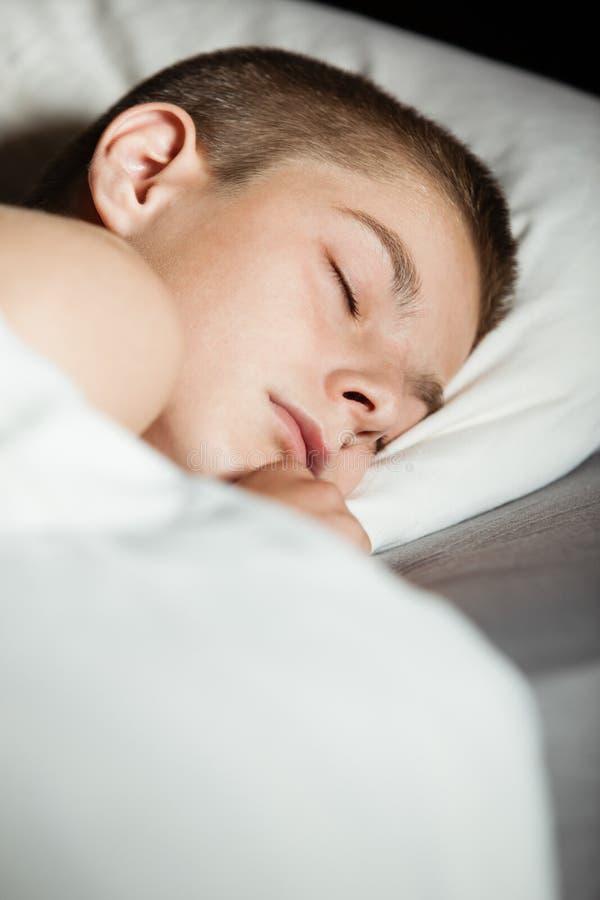 Спать мальчик в кровати с космосом экземпляра стоковые изображения rf