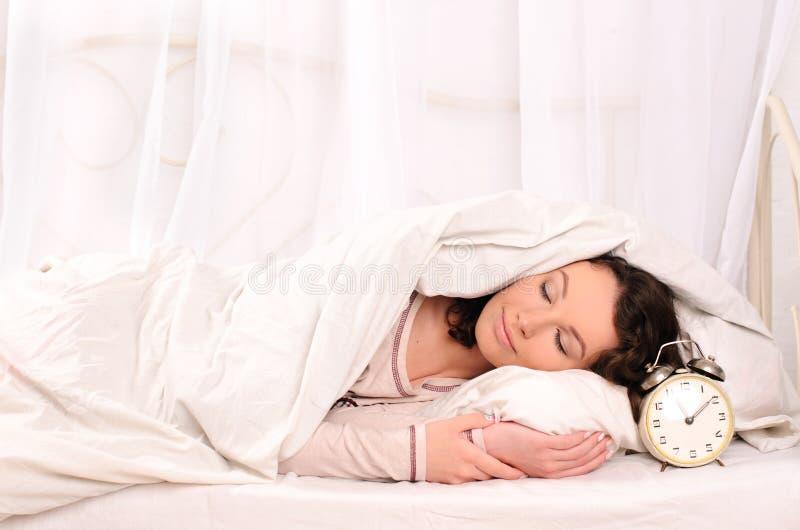 Спать молодая женщина и будильник стоковое изображение rf