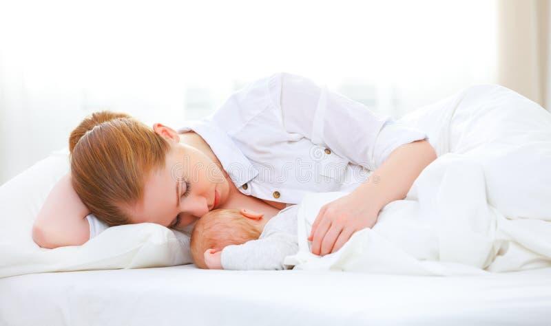 Спать совместно и кормя грудью мать и newborn младенец в b стоковое фото