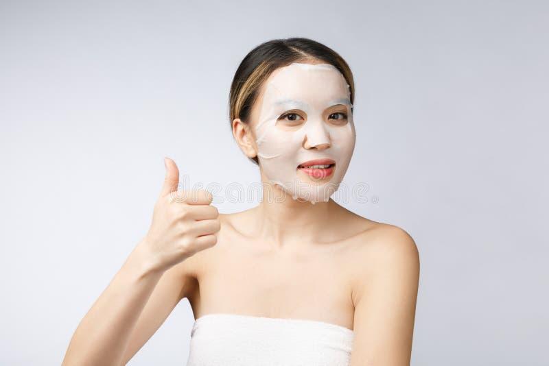 Спа, медицинское соревнование Азиатская девушка с косметической маской с большим пальцем руки показа вверх стоковое изображение